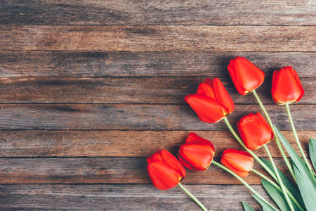 bouquet of red tulips on wooden retro grunge background with copy space. Mothers Day concept, womens day, Top view