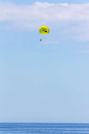 vacationers fly on a yellow parachute on a summer holiday by the sea in the resort