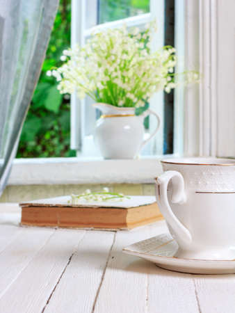 a cup of tea or coffee and a book on a white wooden antique retro table and a bouquet of lily-of-the-valley flowers on a window sill near an open window in a country house in the spring morning