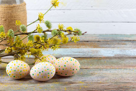 Easter composition of flowering twigs of willow, dogwood and Easter eggs with a pattern of yellow dots on a wooden retro background with a copy of the space close-up Stock Photo