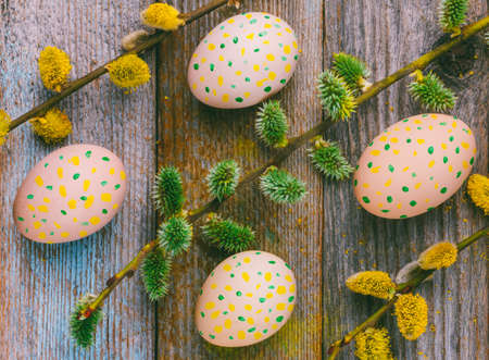 Easter composition of flowering willow twigs and Easter eggs with a simple pattern of yellow and green dots on a wooden retro background top view close-up