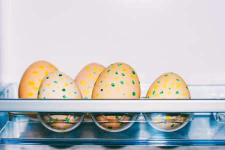 Easter eggs with pattern of yellow and green dots in plastic tray in fridge with copy space closeup
