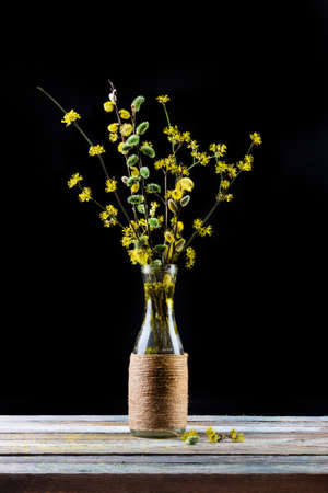 bouquet of flowering branches of willow and dogwood in a vase on the table on a black background