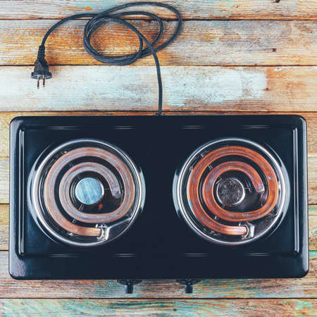electric stove with two electric forks on a wooden table, top view close-up