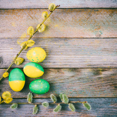 Easter composition of blooming willow twigs and Easter eggs with a pattern of yellow and green color on a wooden retro background with copy space close-up top view