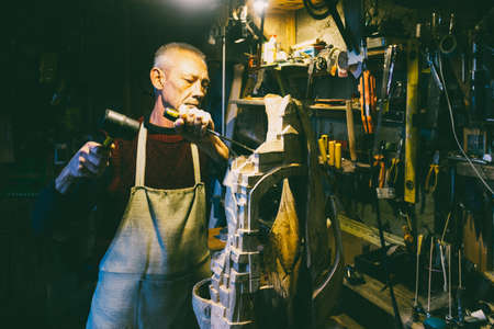 Master carpenter 50 - 55 years old creates wooden sculpture in the workshop