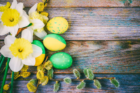 Easter composition of narcissus flower blooming willow twigs and Easter eggs with a pattern of yellow and green color on a wooden retro background with copy space close-up top view Stock Photo