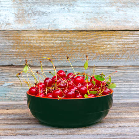 full bowl of ripe cherry berries on a wooden table with copy space Foto de archivo