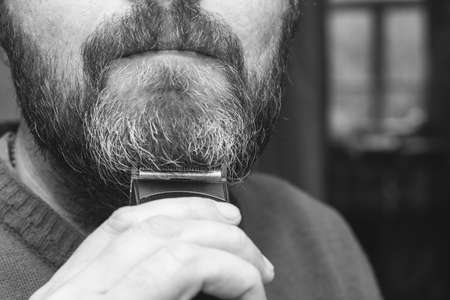a man cuts his gray beard trimmer closeup, black and white photo