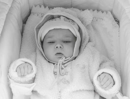 portrait of a sleepy three-month-old baby girl lying in a cradle in pink clothes, top view black and white photo
