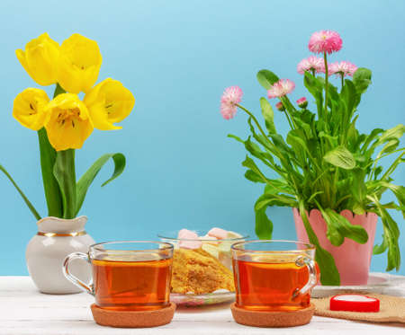 still life with cups of tea, pieces of cake, bouquet of pink flowers in a pink pot, marshmallow and heart-shaped candle and yellow tulips flowers on a white wooden table on blue background