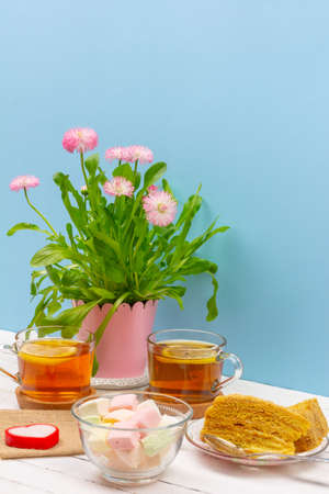 still life with cups of tea, pieces of cake, bouquet of pink flowers in a pink pot, marshmallow and heart-shaped candle on a white wooden table on blue background