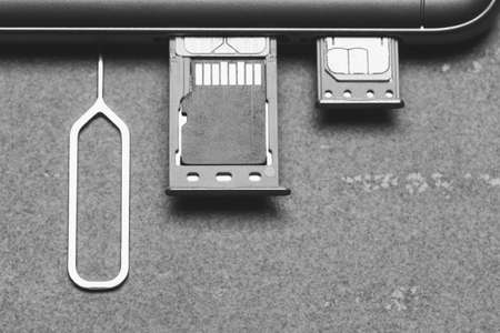 Smartphone with open SIM slots and micro SD memory on a gray background with copy space, top view close-up black and white photography