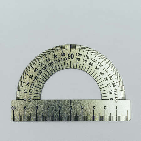 metal protractor close-up on grey background top view