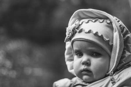 portrait of serious brooding eleven month old baby girl on natural background with copy space, black and white photo 写真素材