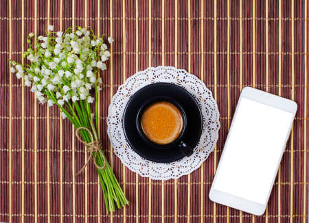 mock up smartphone, black Cup of coffee with milk on a saucer and a bouquet of lilies of the valley on the table, top view flat lay