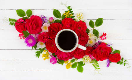 floral summer composition of roses, peonies, cornflowers, green leaves and a Cup of black coffee on a white wooden background, top view flat lay