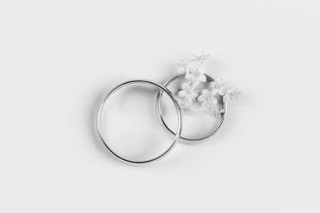 a pair of gold wedding rings and small white flowers in a ring on a white background, top view flat lay, black and white photo