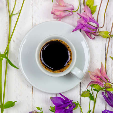 a Cup of black coffee on a saucer and flowers on a white table top view close-up flat lay