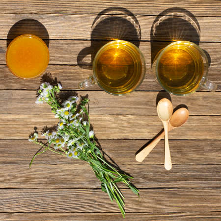 two cups of green tea, honey, a bouquet of chamomile and wooden spoons on the table on a Sunny summer day, top view flat lay