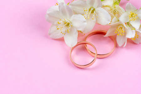 pair of gold wedding rings and white Jasmine flowers on pink background with copy space