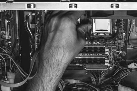 Maykop, Russia - September 17, 2016: male hand installs an Intel processor in the socket on the motherboard, black and white photo