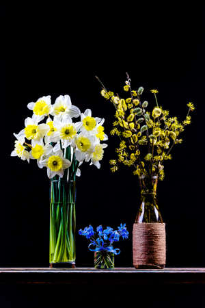 bouquet of flowering branches of willow and dogwood in a vase, bouquet of narcissus flower and bouquet of bluebell flower in a vaset on the table on a black background Imagens