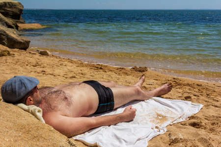 a man 30 - 40 years old in a cap, swimming trunks and sunglasses lying sunbathing on a sandy beach and looking at the sea on a hot summer day Reklamní fotografie