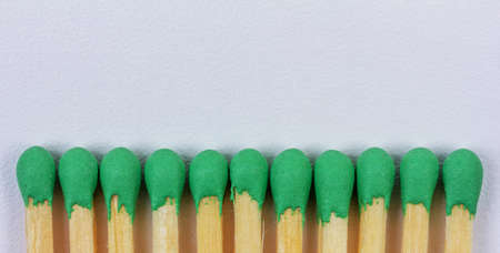 wooden matches with green sulphur on grey background with copy space closeup, top view