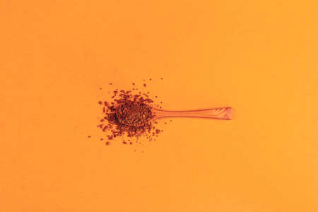 wooden spoon with instant granulated coffee on a background of neo carrot color top view, minimal art