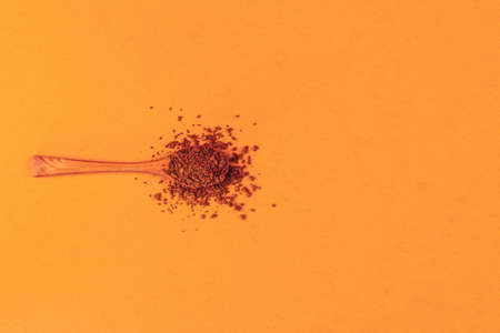 wooden spoon with instant granular coffee on a neo-carrot color background top view with copy space, minimal art