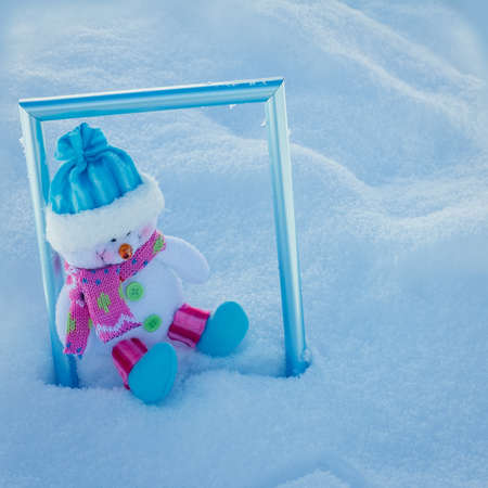 Christmas toy snowman in a blue cap sitting on the snow in a snowdrift in a blue photo frame close up Stock Photo
