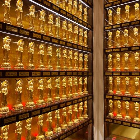 Hainan Island, Sanya, China - August 19, 2019: a showcase with golden souvenir statuettes of the goddess Guanyin in a gift shop Redakční
