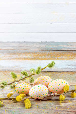 Easter spring still life of flowering willow branches and eggs on a retro wooden table on a white background with a copy space