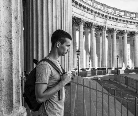 profile portrait of a wicked young man with a backpack standing next to the columns of the Kazan Cathedral in St. Petersburg, black and white photo Stockfoto