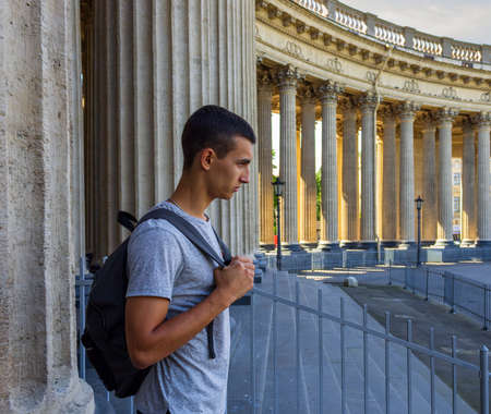 profile portrait of a wicked young man with a backpack standing next to the columns of the Kazan Cathedral in Saint Petersburg