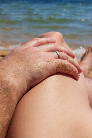 a mans hand with a gold wedding ring lies on a womans hip against the blue sea Zdjęcie Seryjne
