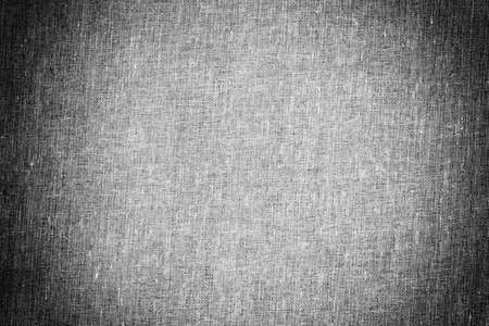 background texture of grey canvas fabric with vignette, black and white photo 免版税图像