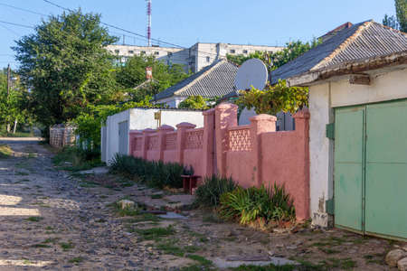 an unpaved street with a pink brick fence on the outskirts of a provincial town on a Sunny summer morning