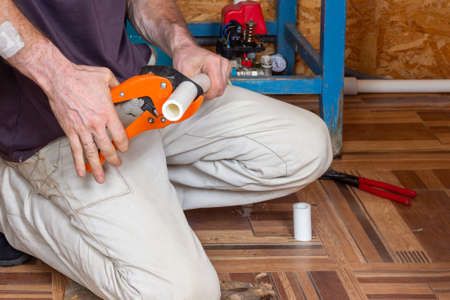 Installation of heating or water supply systems. A male plumber cuts polypropylene plastic pipes with scissors to solder a water pipe