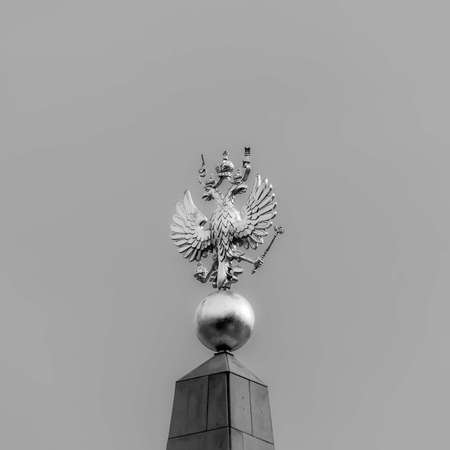 Golden double-headed eagle against the grey sky black and white photo 写真素材