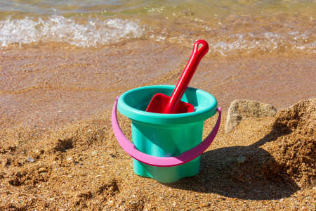plastic children's toy bucket with a scoop on the sandy shore of the sea beach on a sunny summer day Standard-Bild