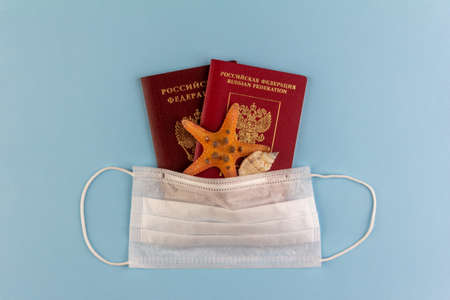 two Russian passports, a starfish and a seashell under a disposable medical mask on a blue background close-up view from above, the concept of self-isolation during the coronavirus COVID-19 pandemic 写真素材