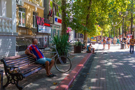 Kerch, Russia - 13 August 2019: a man is sitting on a bench listening to a street musician and pedestrians tourists are walking along the street of the resort city of Kerch on a summer day