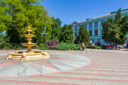 Kerch, Russia - 13 August 2019: a janitor removes garbage on the square with a fountain on a summer day 報道画像