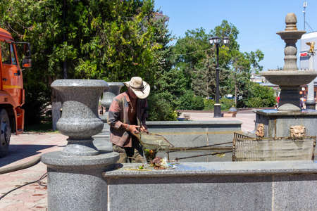 Kerch, Russia - 13 August 2019: a male janitor removes trash from a fountain on a summer day 報道画像