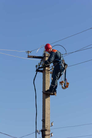 Krasnodar, Russia - March 2, 2020: work electrician on top of a pole mount a new line of electrical wires against a blue sky
