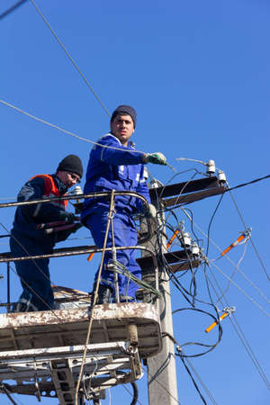 Krasnodar, Russia - March 2, 2020: male electricians change electrical wires on poles