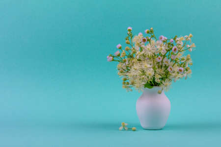 beautiful bouquet of wild flowers chamomile and clematis in a white jug on a blue green background closeup with a copy space
