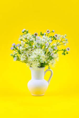 beautiful bouquet of wild flowers chamomile and clematis in a white jug on a yellow background close up